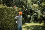 Image shows a man using the STIHL HLA 56 hedge trimmer on a angle for easy cutting of the top of a tall hedge