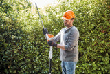 Image showing a man wearing safety goggles, a hard hat and gloves, safely changing the angle of the HLA 56 battery powered hedge trimmer