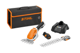 STIHL HSA 26 Hedge Trimmer cut including STIHL Handheld battery operated hub with seperate grass trimmer and shrub cutter attachments. Image also shows the charger, battery and STIHL carry case in black with orange trim