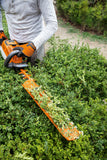 A man using the STIHL HSA 86 Hedge Trimmer to trim the top of a bush