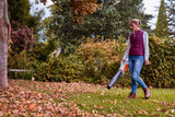 A woman using the BGA 57 STIHL blower to clear away leaves and debris in a garden. She is wearing safety clothing