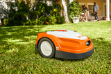 STIHL RMI 422 P Orange Robotic Mower shown in a garden