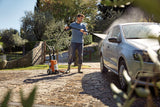 STIHL RE 100 Pressure Washer being used by a man to clean a silver car on his driveway