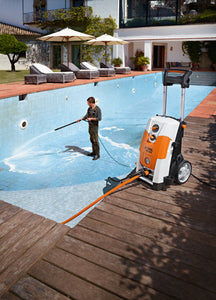The STIHL RE 143 PLUS Pressure Washer being used by a man in overalls cleaning the inside of a swimming pool