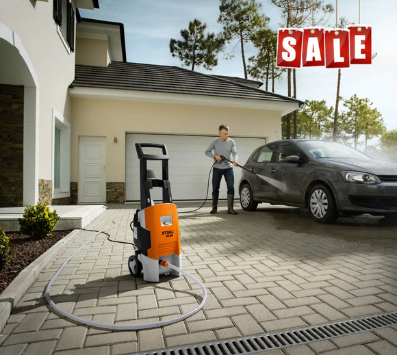 STIHL RE 98 Pressure Washer being used by a man to clean his grey car on a brick driveway in front of a house