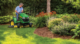 Man on a John Deere X585 petrol alwn mower with side discharge deck. Making use of the 4 wheel steer option cutting a lawn in a tight corner.