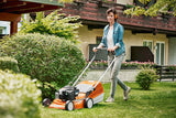 The STIHL RM 248 T Walk Behind / Push Mower being used by a lady in a denim jacket in her garden, wearing ear protectors