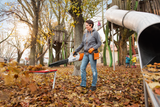 A woman using the BGA 100 cordless blower. She is using it to easily clear leaves of a bench. Wearing appropriate safety clothing including gloves and safety glasses.