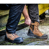 A man wearing the Buckler safety lace up boot in dark brown in wet conditions