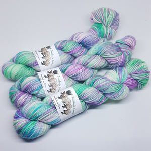 Double knitting (DK) handdyed yarn in a variegated pastel colourway with purples, mint greens and aqua colours.