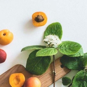 Photo of leaves, fruit and a wood chopping board