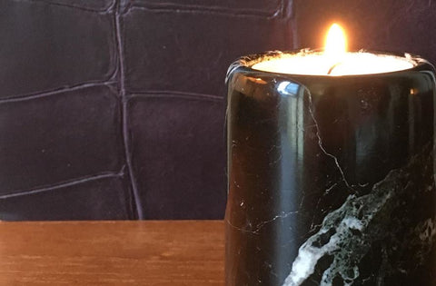 A burning scented candle in a black marble candle holder