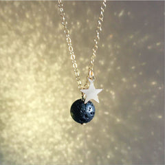 A moon and star necklace on a glittering gold background