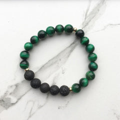A green tigers eye bracelet on a white marble background