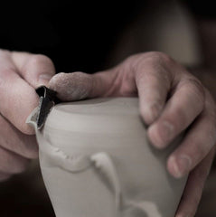 Man making a clay pot by hand