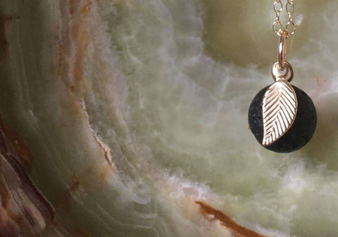 A lava diffuser necklace on an onyx stone background