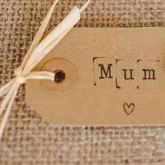 """A card gift tag with the word """"mum"""" written on it"""