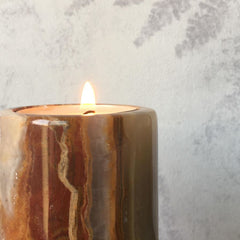 Solid Onyx stone candle in front of fern wallpaper