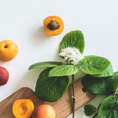 Fruit, leaves and a wooden chopping board