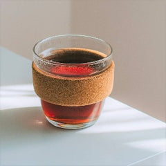A reusable glass coffee cup