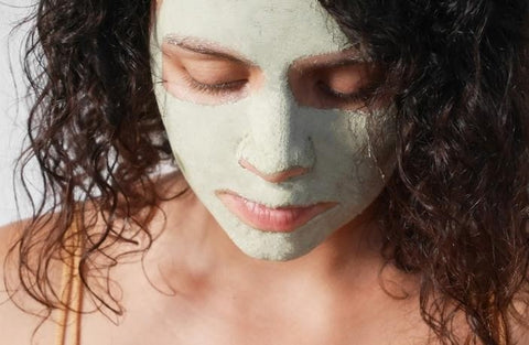 Woman wearing a green clay face mask