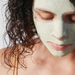 A woman wearing a green clay face mask