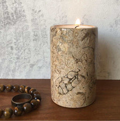 A fossil stone candle holder on a bedside table