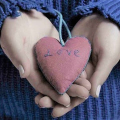 """A woman holding a pink heart cushion with the word """"love"""" stitched on to it"""