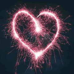 A pink heart written in the air with a sparkler