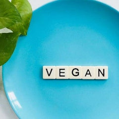 """A blue plate with the word """"vegan"""" written on it"""