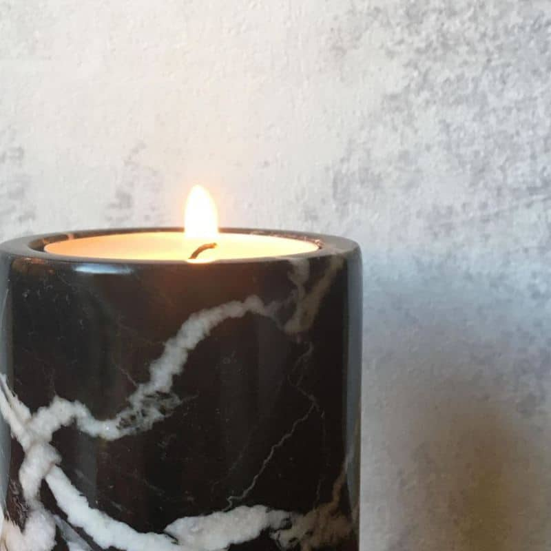 Black marble tea light candle holder with a lit candle