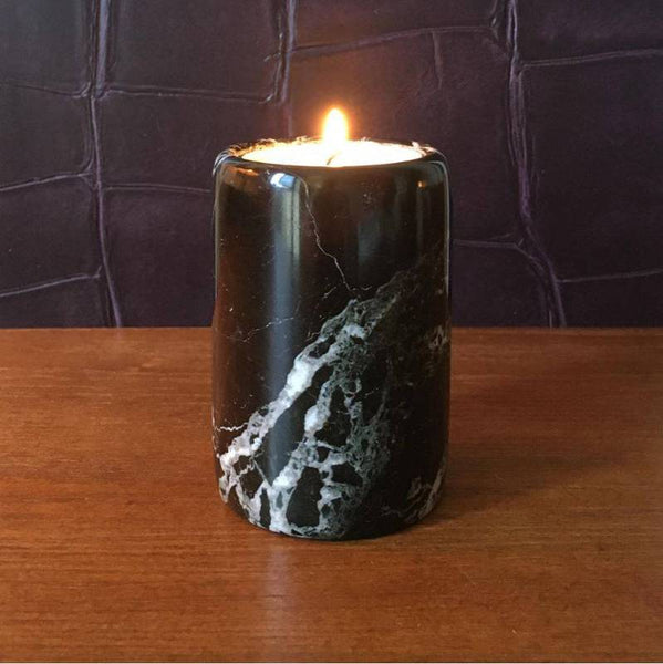 Black marble tea light candle holder on a wooden surface with a lit candle