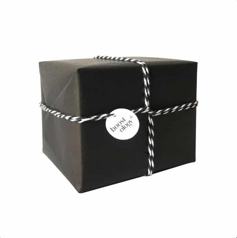 A present wrapped in black kraft paper and tied with decorative cotton string