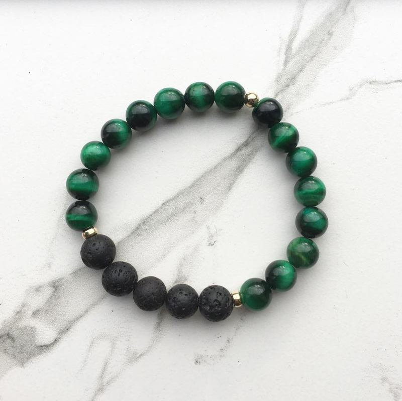 Green tigers eye lava diffuser bracelet on a white marble background