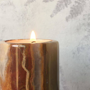 Onyx stone tea light candle holder, with a lit tea light candle