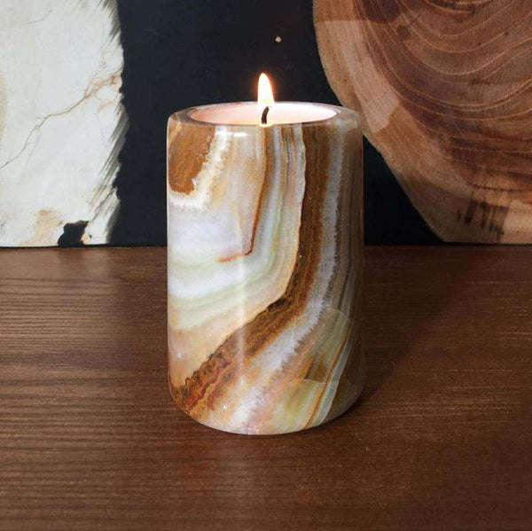 Onyx stone tea light candle holder on a wooden unit, with a lit tea light candle