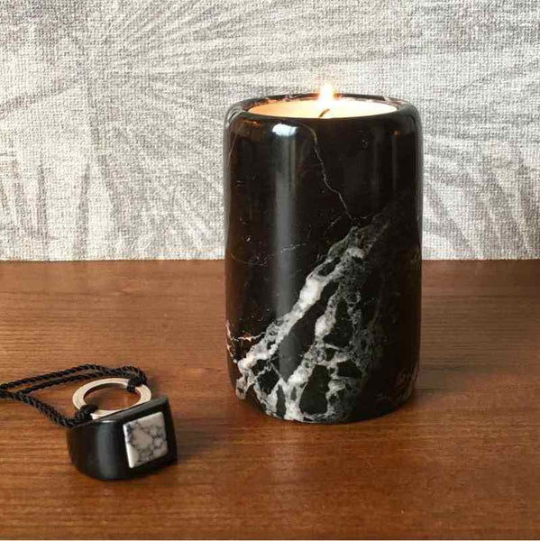 Black marble tea light candle holder next to some jewellery with a lit candle