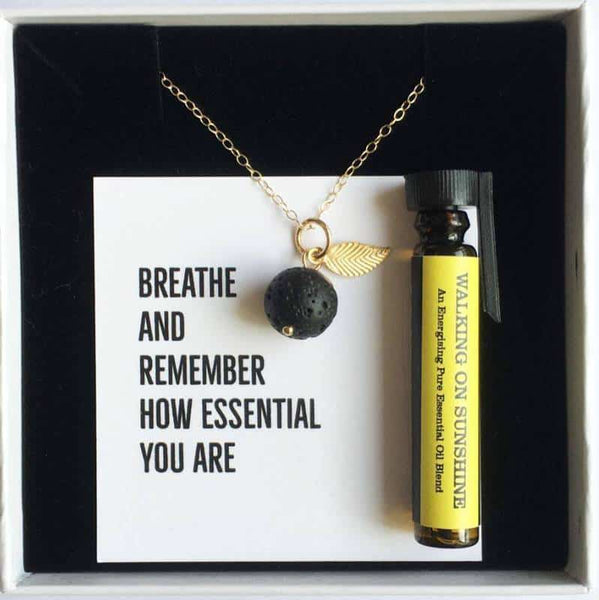 Gold leaf lava diffuser necklace with a small bottle of essential oil