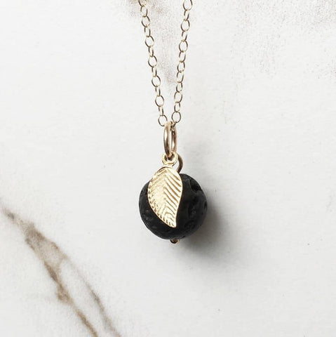 Gold leaf lava diffuser necklace on a white marble background