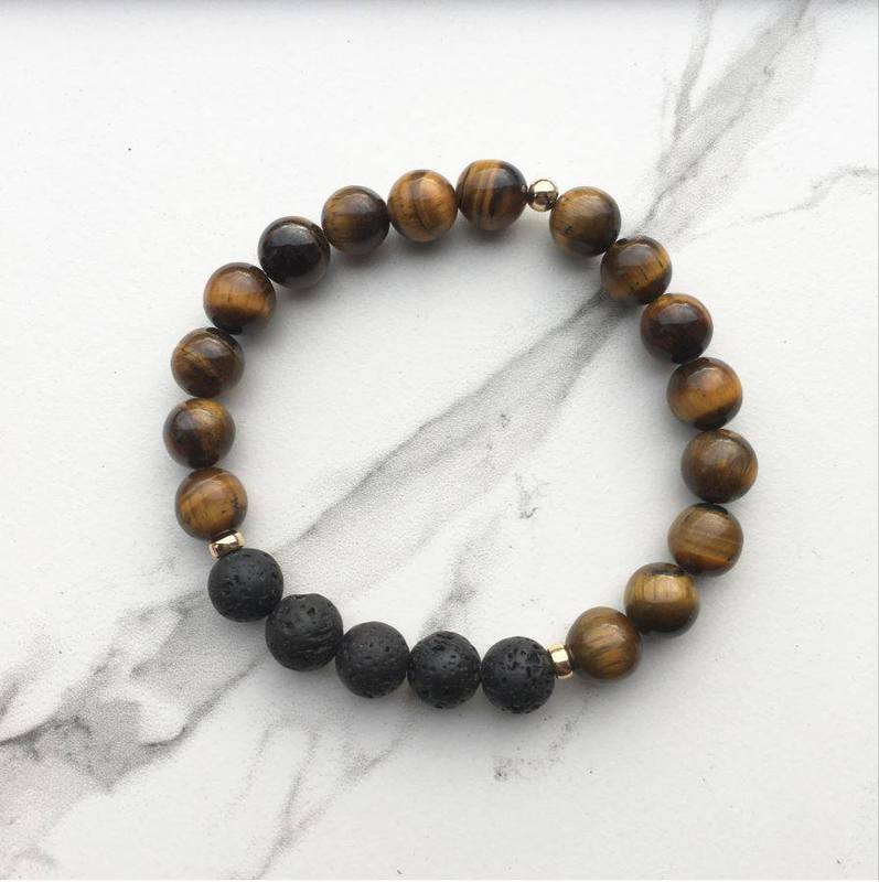 Tigers eye and lava diffuser bracelet on a white marble background
