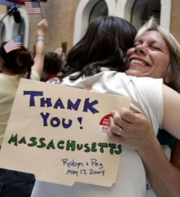 Same-sex couples began marrying in Massachusetts on May 17, 2004. Thank You Massachusetts hug sign between wed lesbian couple  ⁠