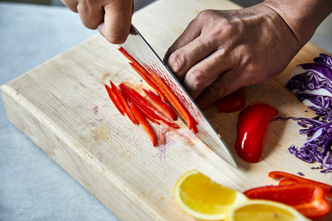 Chef's hand cutting red peppers on a light wooden board