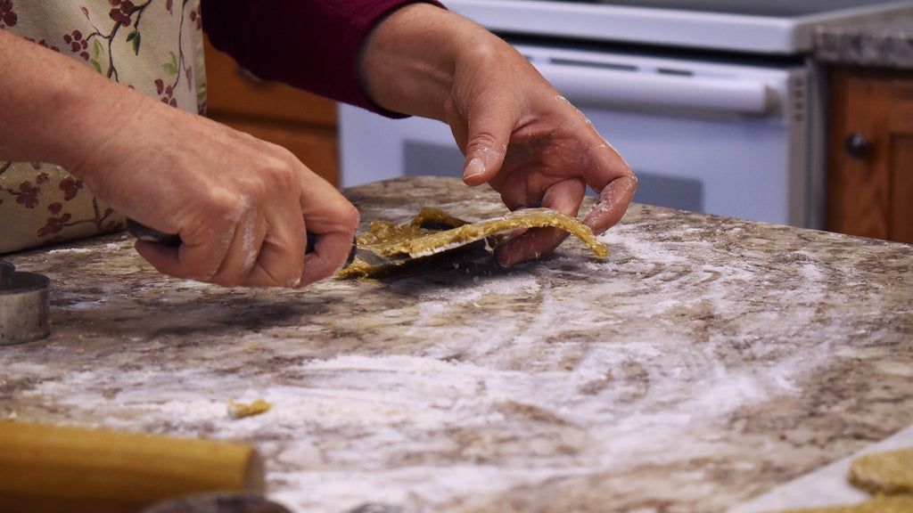 A person rolling and cutting cookies at a floured countertop.