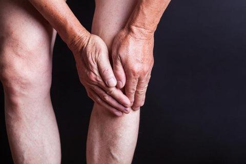 senior person holding knee in pain