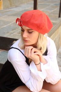 Orange linen beret with brooch.