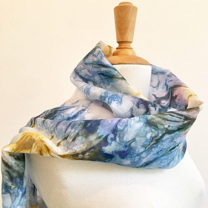 Hand painted blue silk scarf with an abstract flower design. Pure silk foulard in blue and gold