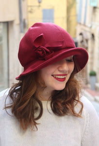 Burgundy cloche hat with asymmetric brim and handmade fabric flower.