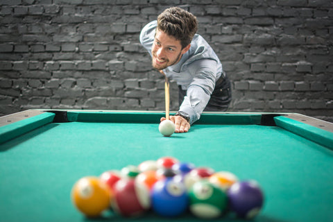 Happy business man playing a game of billiards