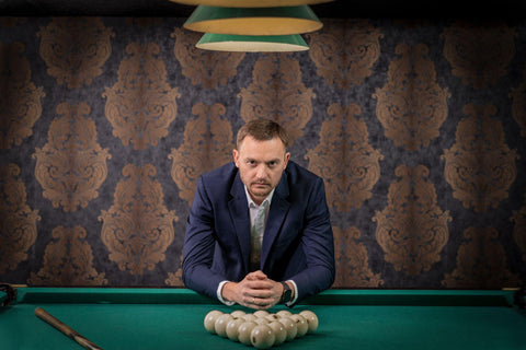a man has placed balls on the pool table and is ready to play a game