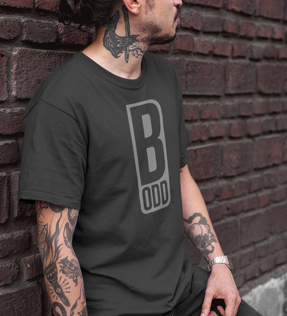 Tatooed man wearing B Odd t-shirt in grey leaning against brick wall.
